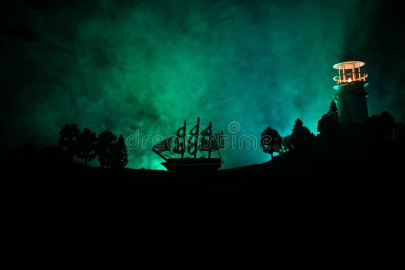 Vieja navegación de madera del buque de guerra por noche cerca del faro o faro y velero Fondo de niebla oscuro Foco selectivo fotos de archivo
