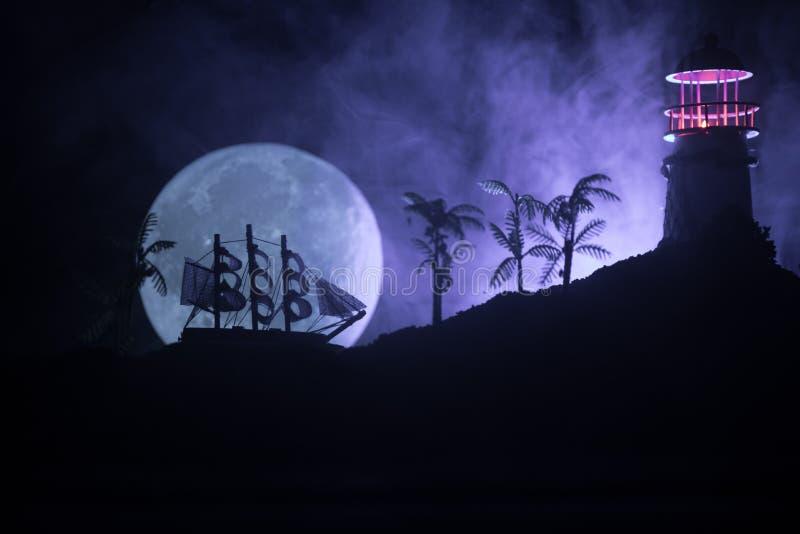 Vieja navegación de madera del buque de guerra por noche cerca del faro o faro y velero Fondo de niebla oscuro Foco selectivo fotografía de archivo