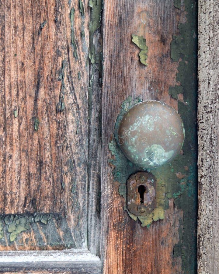 Vieja peladura, puerta de madera con el botón de puerta viejo del metal fotos de archivo