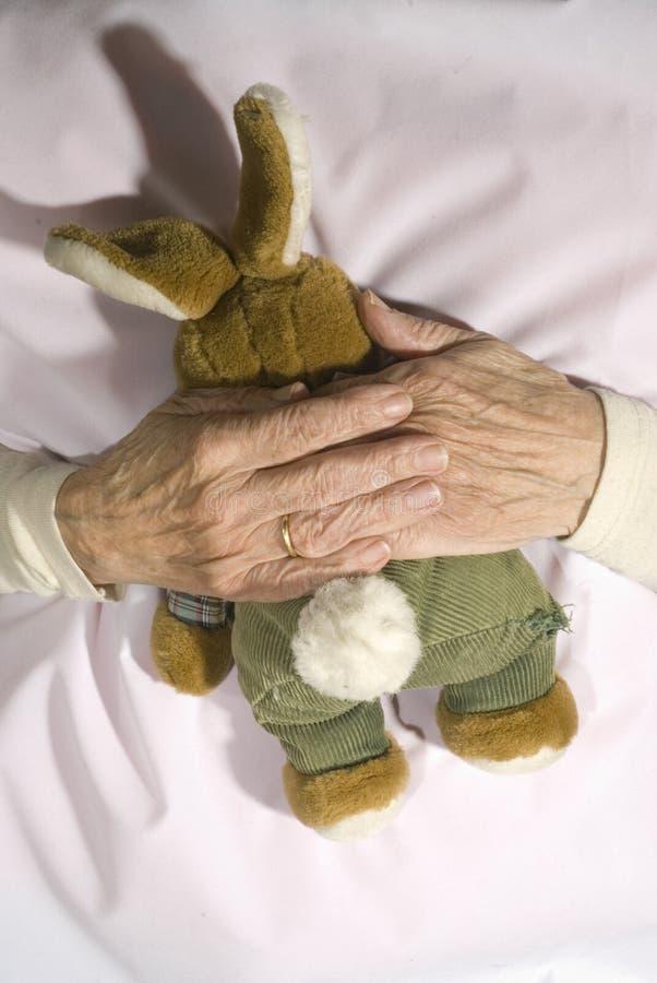 Vieja persona demente con el conejo relleno imágenes de archivo libres de regalías