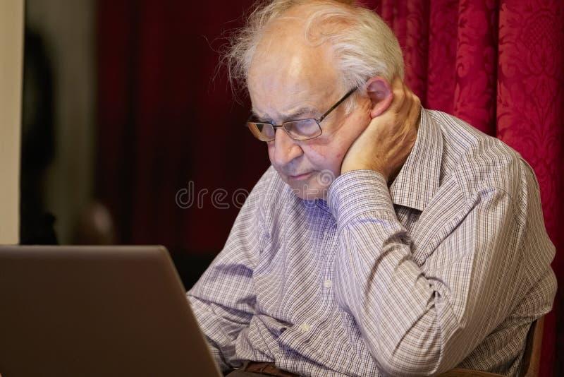 Vieja persona mayor mayor que aprende el ordenador y destrezas en línea de Internet para prevenir fraude foto de archivo