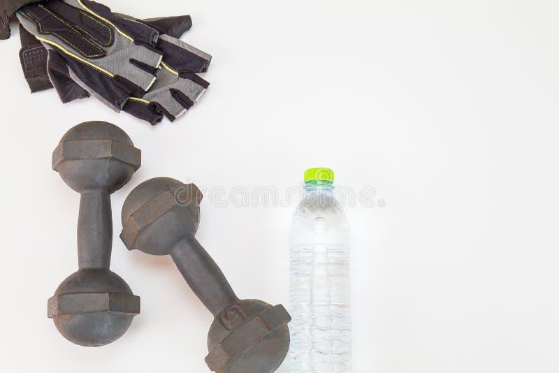 Vieja pesa de gimnasia, arboleda de la aptitud y botella de agua del plástico en el fondo blanco fotos de archivo
