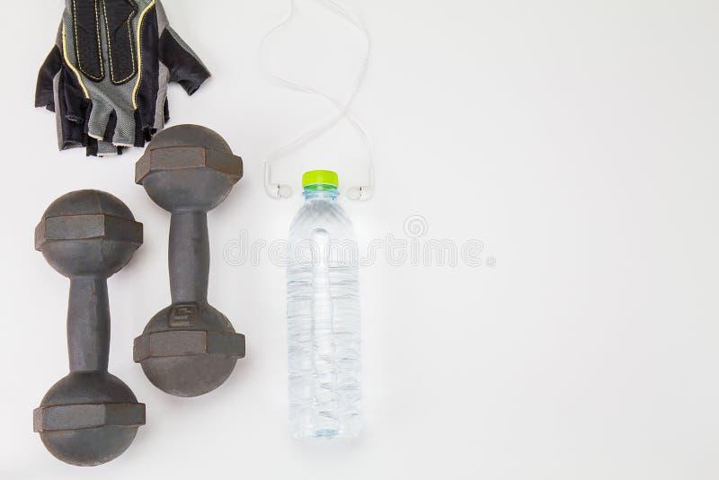 Vieja pesa de gimnasia, arboleda de la aptitud y botella de agua y auricular interno del plástico en el fondo blanco imagen de archivo libre de regalías