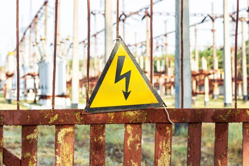 Vieja placa de metal oxidada envejecida del triángulo del primer con la señal de peligro de alto voltaje Central eléctrica con lo fotografía de archivo