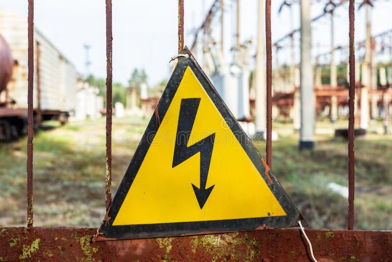 Vieja placa de metal oxidada envejecida del triángulo del primer con la señal de peligro de alto voltaje Central eléctrica con lo fotografía de archivo libre de regalías