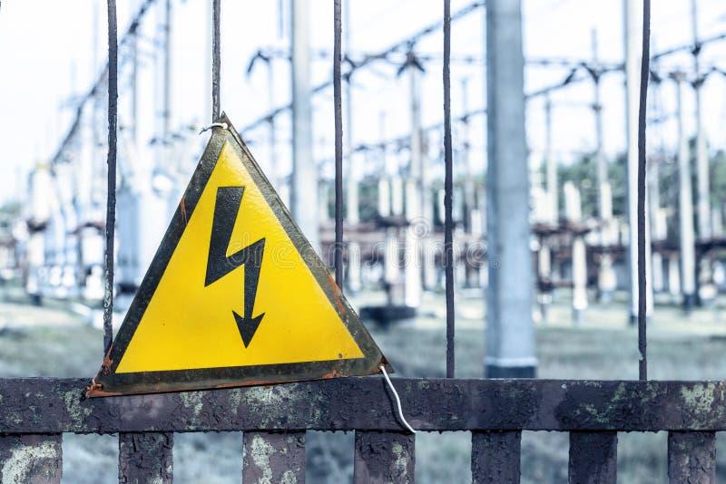 Vieja placa de metal oxidada envejecida del triángulo del primer con la señal de peligro de alto voltaje Central eléctrica con lo foto de archivo
