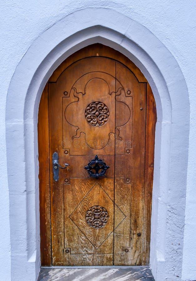 Vieja puerta principal de madera con un golpeador de puerta decorativo imágenes de archivo libres de regalías