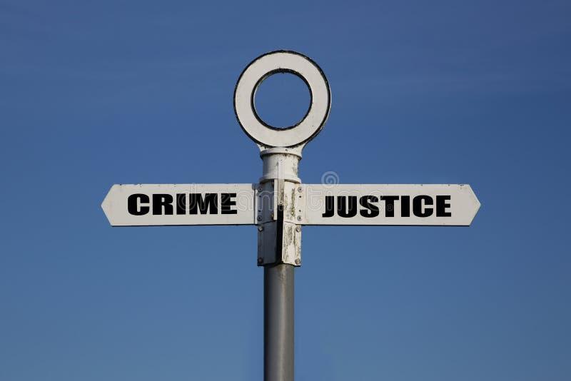Vieja señal de tráfico con crimen y justicia que señala en direcciones opuestas fotos de archivo