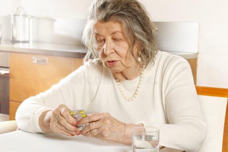 Vieja sentada en una mesa tomando píldoras imagen de archivo libre de regalías