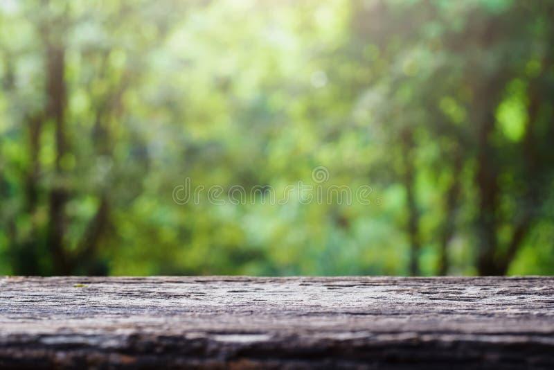 Vieja sobremesa de madera en fondo abstracto borroso verde del fondo del follaje Listo nos utilizó exhibición o montaje foto de archivo libre de regalías