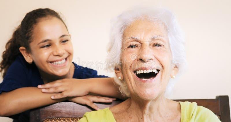 Vieja sonrisa mayor feliz de la abuela y de la chica joven de la mujer imagen de archivo libre de regalías
