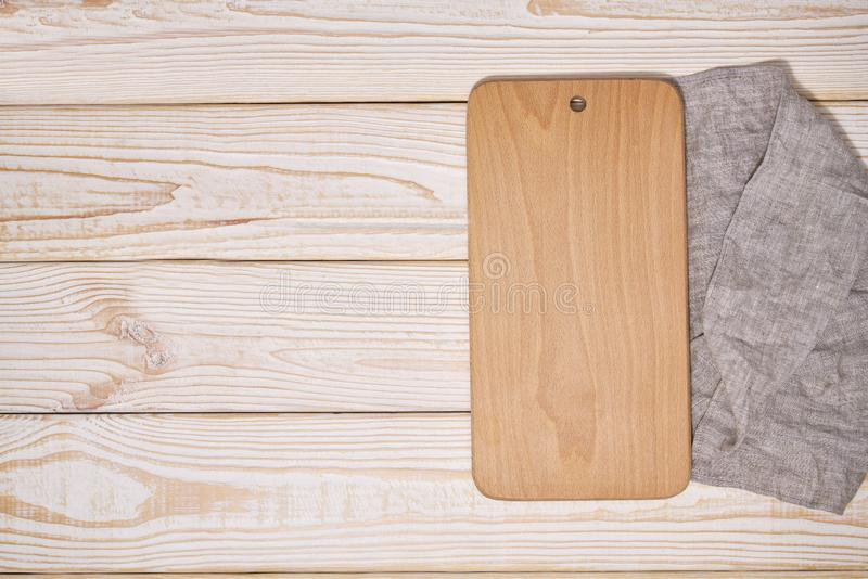 Vieja tabla de cortar de madera vacía en el fondo de madera blanco, visión superior foto de archivo libre de regalías