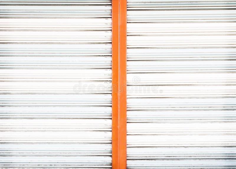 Vieja textura de acero rodante blanca y anaranjada de la puerta para el fondo foto de archivo libre de regalías