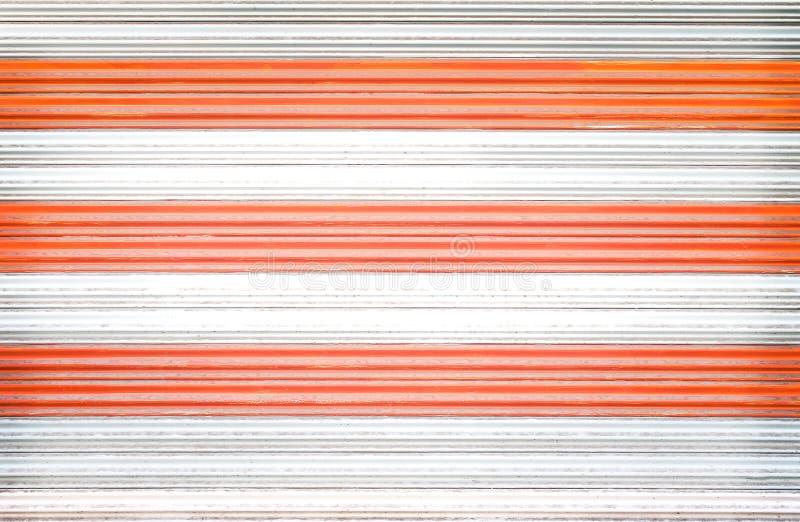 Vieja textura de acero rodante blanca y anaranjada de la puerta para el fondo fotos de archivo libres de regalías