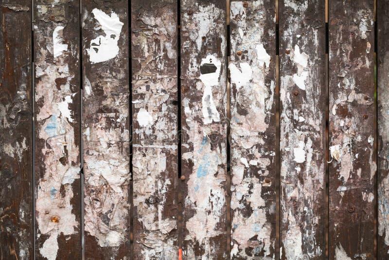 Vieja textura de la cerca con los pedazos de los anuncios del papel imagenes de archivo
