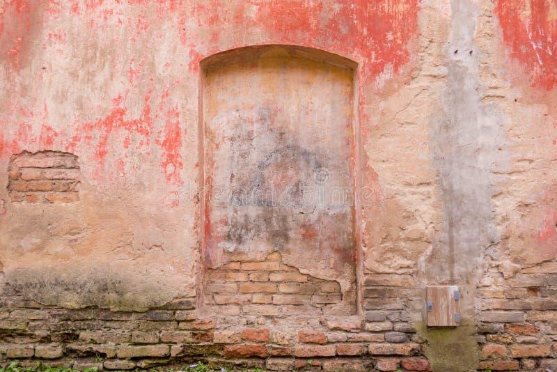 Vieja textura pintada resistida del fondo de la pared La pared pelada sucia roja del yeso con caerse forma escamas de la pintura foto de archivo