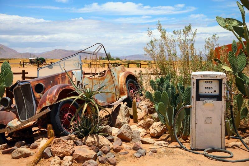 Vieja y oxidada ruina del coche en una estación del gaz del vintage imagenes de archivo