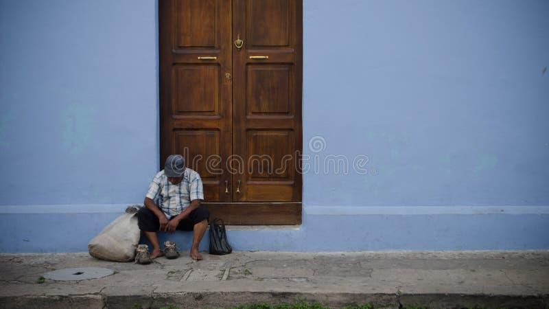 Vieja y triste sentada sin hogar en la calle fotografía de archivo
