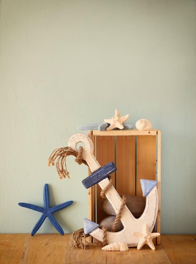 Viejas ancla y cáscaras de madera náuticas en la tabla de madera sobre fondo de madera de la aguamarina fotografía de archivo