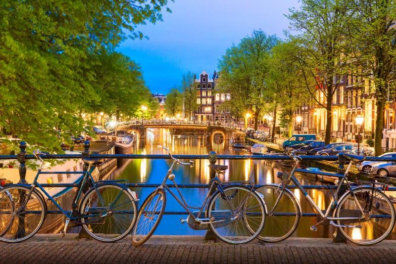 Viejas bicicletas en el puente de Amsterdam, Países Bajos contra un canal durante el verano crepúsculo atardecer Vista emblemátic foto de archivo libre de regalías