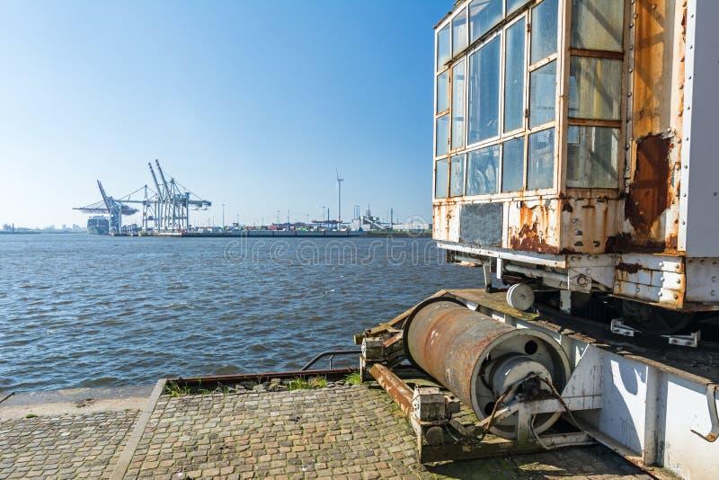 Viejas instalaciones del puerto en el muelle en Hamburgo con la terminal de contenedores en el fondo imagen de archivo libre de regalías