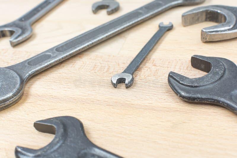 Viejas llaves inglesas en una tabla de madera imagen de archivo