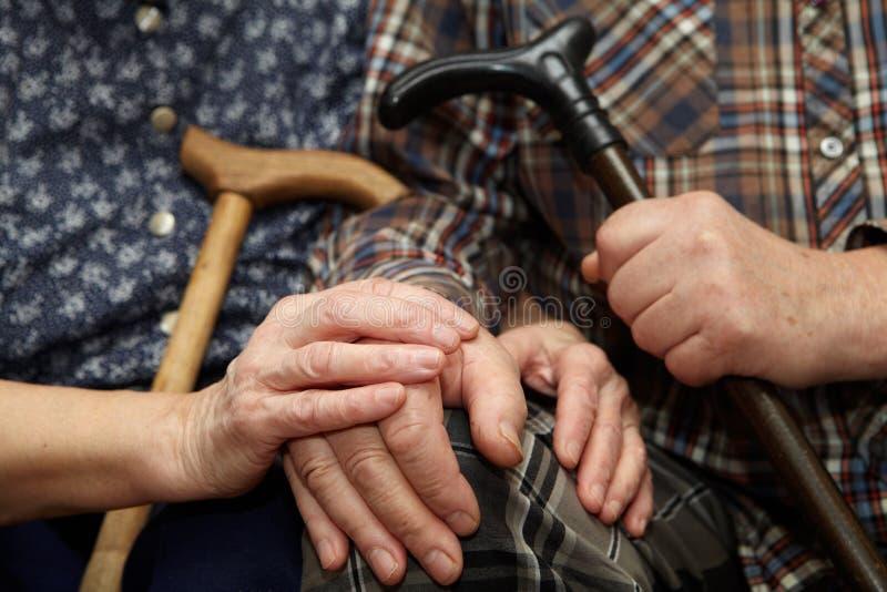 Viejas manos de los pares con el bastón fotos de archivo