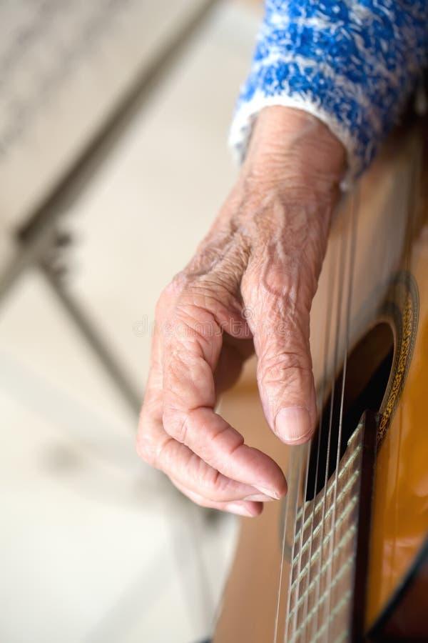 Viejas manos en la guitarra fotografía de archivo