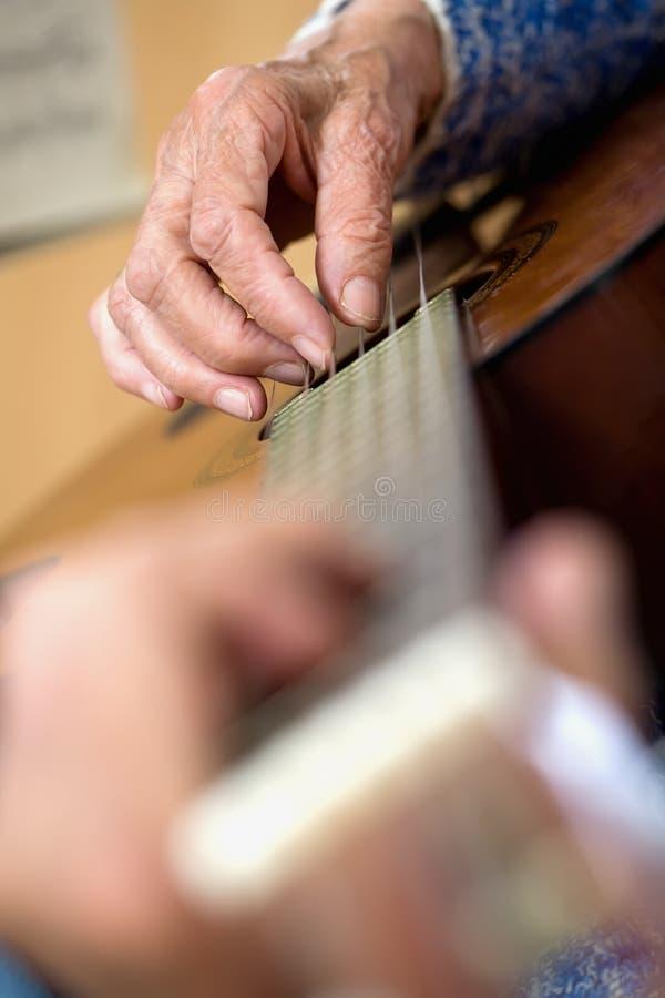Viejas manos en la guitarra imagen de archivo