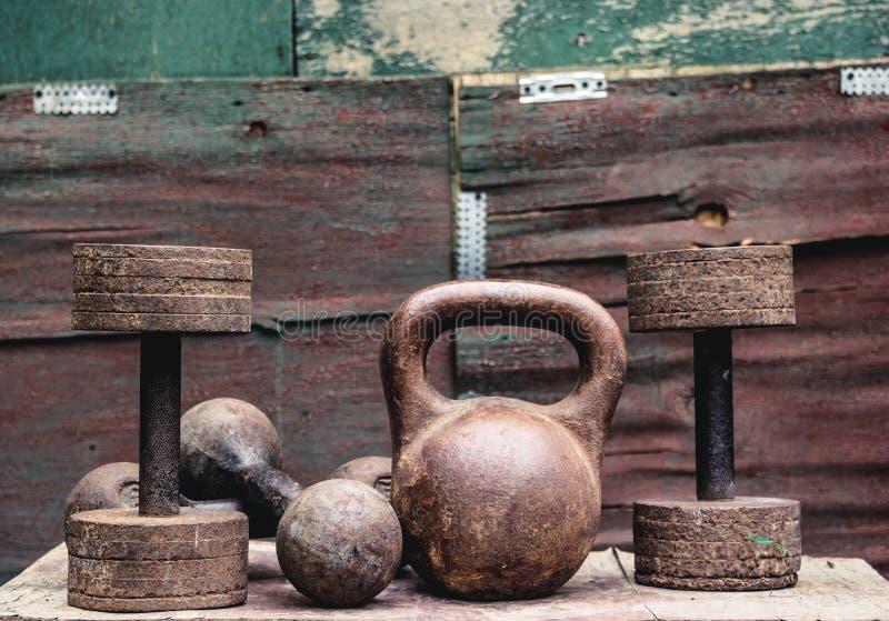 Viejas pesas de gimnasia oxidadas Pesas de gimnasia del vintage en un viejo fondo de madera Forma de vida y deporte sanos imagen de archivo libre de regalías