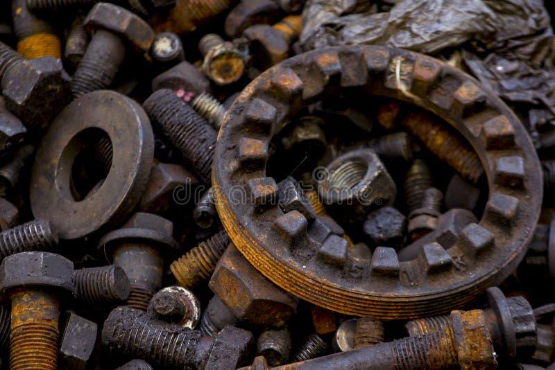 Viejas porciones oxidadas de los tornillos en el material de la pila foto de archivo