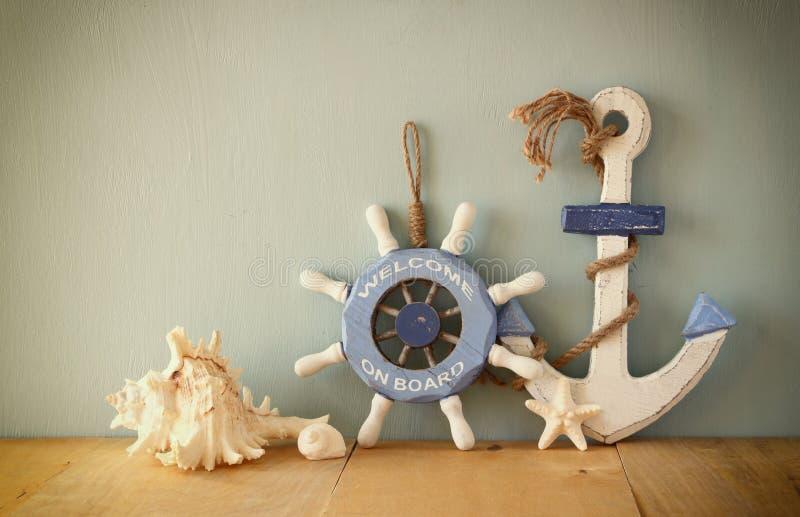 Viejas rueda, ancla y cáscaras de madera náuticas en la tabla de madera sobre fondo de madera imagen filtrada vintage fotos de archivo