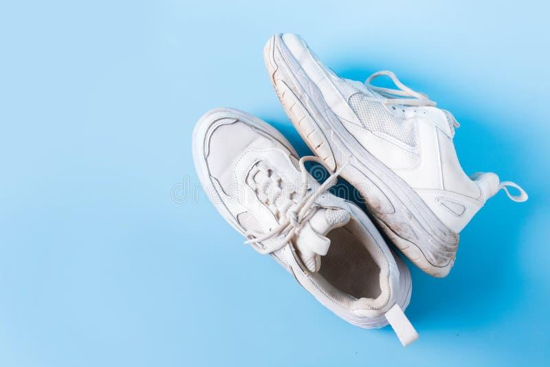 Viejas zapatillas blancas sucias sobre azul foto de archivo