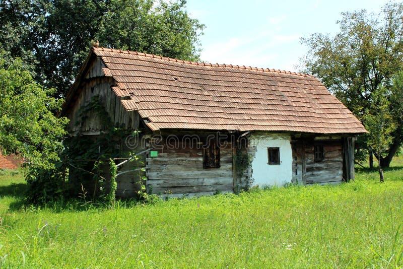 Viejo abandonó la casa de madera de la familia necesitando la restauración seria rodeada con la alta hierba sin cortar y los árbo fotos de archivo libres de regalías