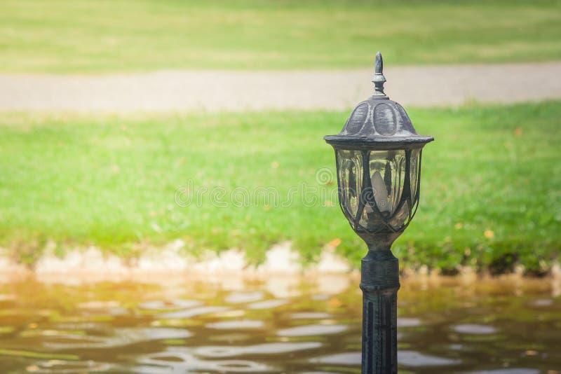 Viejo ajuste de la lámpara de calle del metal en piso concreto al lado de la calzada en el camino y río en estilo del vintage fotografía de archivo libre de regalías