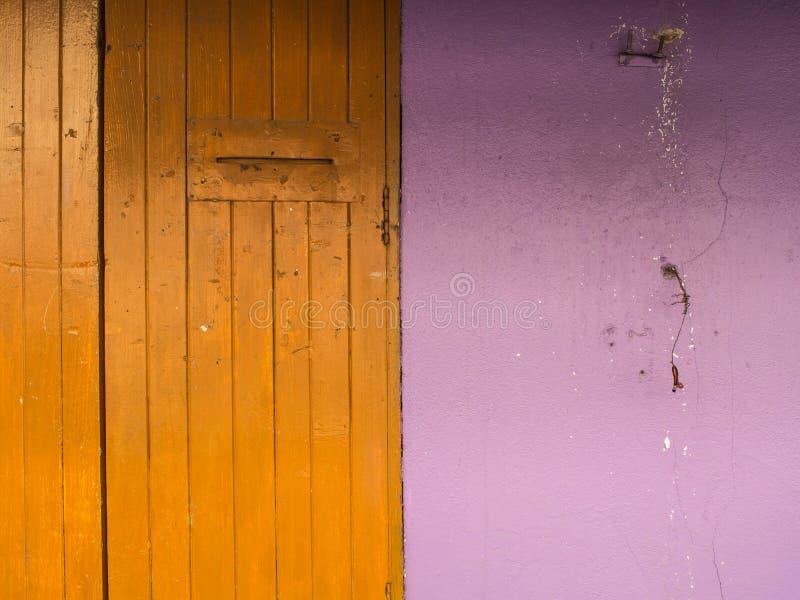 Viejo amarillo de la puerta con la pared púrpura foto de archivo