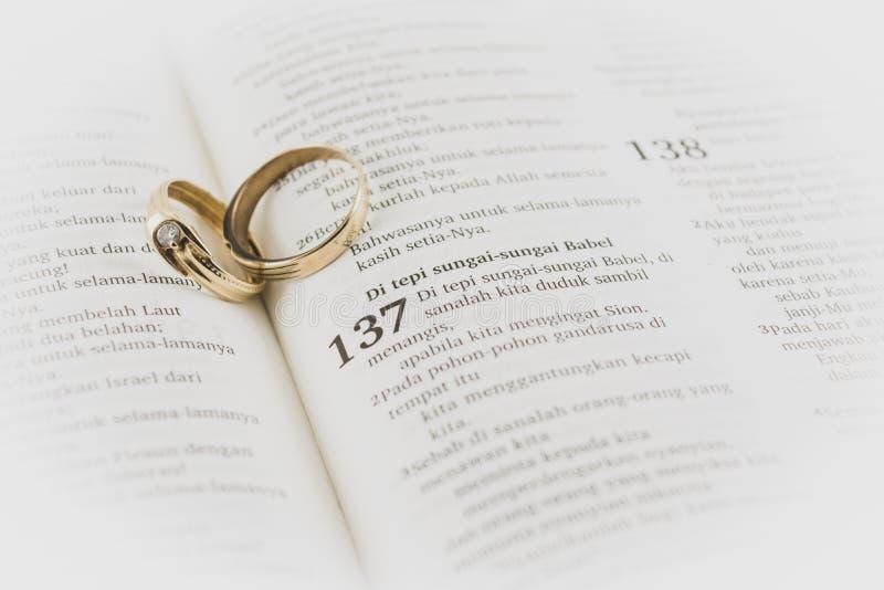 viejo anillo de boda entre la página de la Santa Biblia, símbolo de lealtad y matrimonio largo tono mate fotografía de archivo