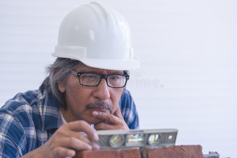 Viejo artesano del constructor que nivela la pared de ladrillo imagen de archivo libre de regalías