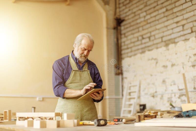 Viejo artesano hermoso que busca la información de la red fotografía de archivo libre de regalías