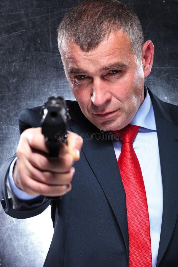 Viejo asesino en traje y lazo que señalan su arma fotografía de archivo libre de regalías