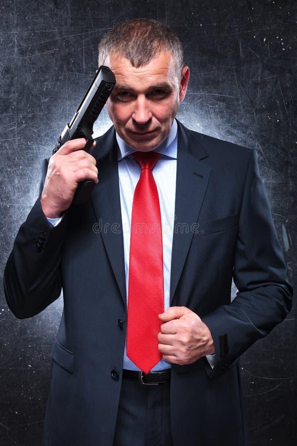 Viejo asesino sonriente que lleva a cabo su arma y la tracción de su traje imágenes de archivo libres de regalías