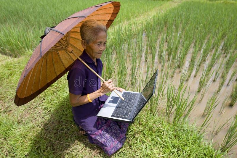 Viejo asiático con la computadora portátil imagen de archivo libre de regalías