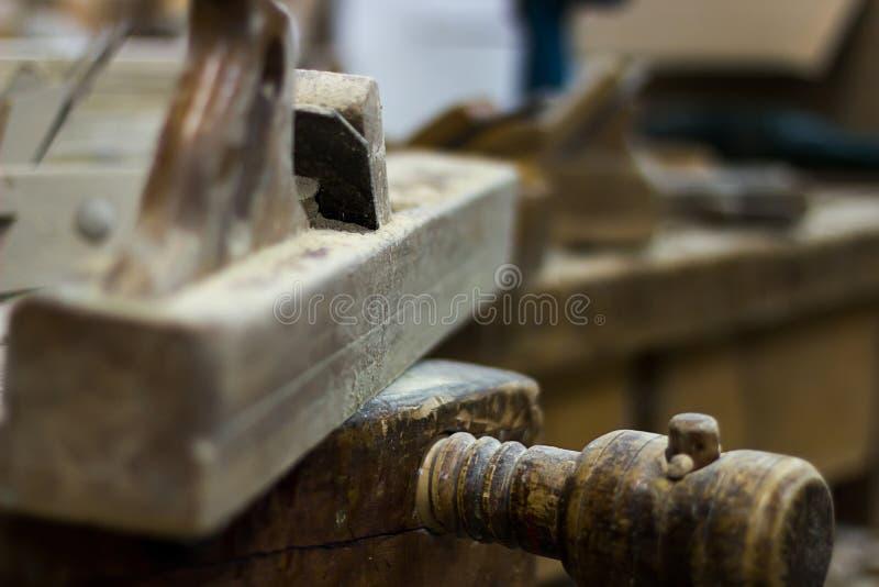 Viejo avión en una alisadora de madera del banco de trabajo del carpintero, avión de la mano fotos de archivo libres de regalías