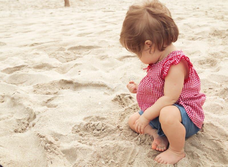 Viejo bebé de nueve meses que se sienta en la playa en día de verano hermoso Poco bastante niño infantil europeo lindo con imágenes de archivo libres de regalías