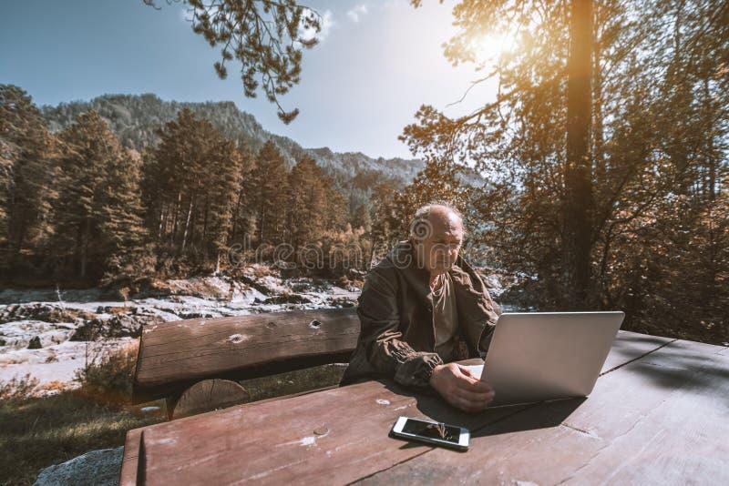 Viejo cazador con su ordenador portátil en montañas imagen de archivo libre de regalías