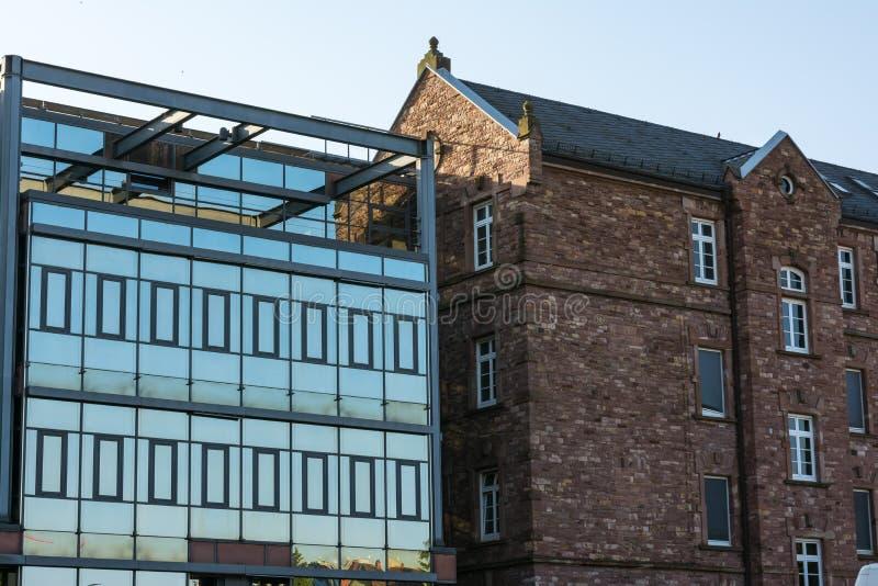Viejo contra el edificio de la nueva comparación de la arquitectura y el lado de cristal del ladrillo imagen de archivo libre de regalías