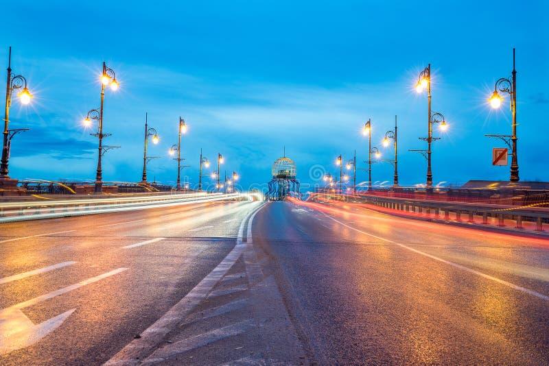 Viejo ` de Staromiejski del ` del puente de la ciudad con los rastros de la luz y torre de observación en la salida del sol imagen de archivo