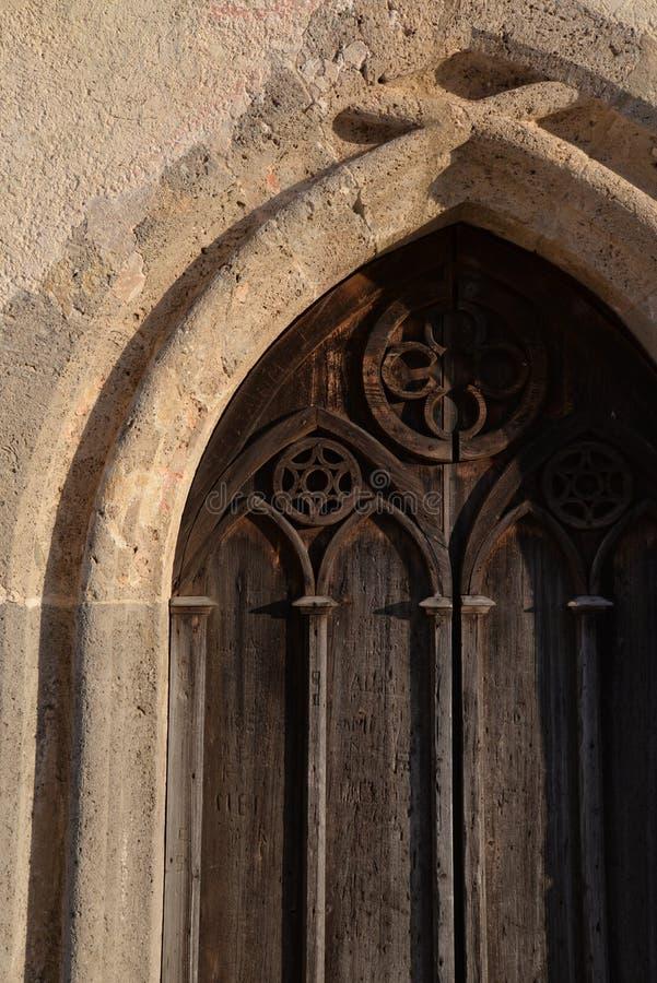 Viejo detalle gótico de madera de la puerta de la iglesia imagenes de archivo
