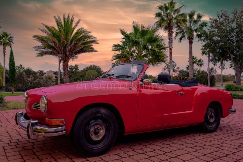 Viejo el vintage aparcamiento en automóvil tropical de la vida de la playa de la puesta del sol de la última hora de la tarde del foto de archivo