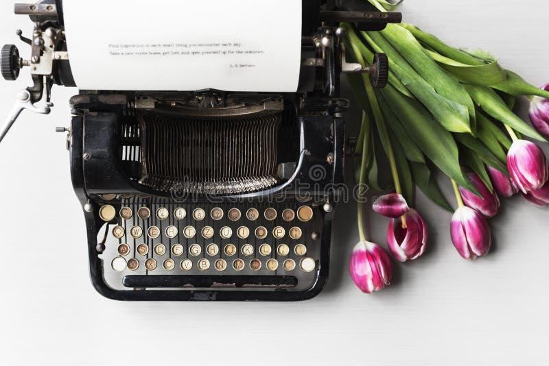 Viejo estilo de la máquina retra de la máquina de escribir por la flor de los tulipanes imagen de archivo